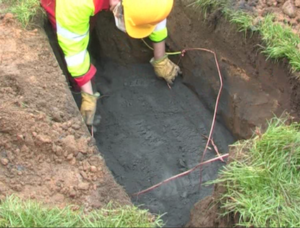 The roadside excavation for a broadband cabinet with Conducrete in the base and 16mm wire earth ring being installed