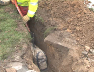 The roadside excavation for a broadband cabinet with bag of Conducrete in the duct trench